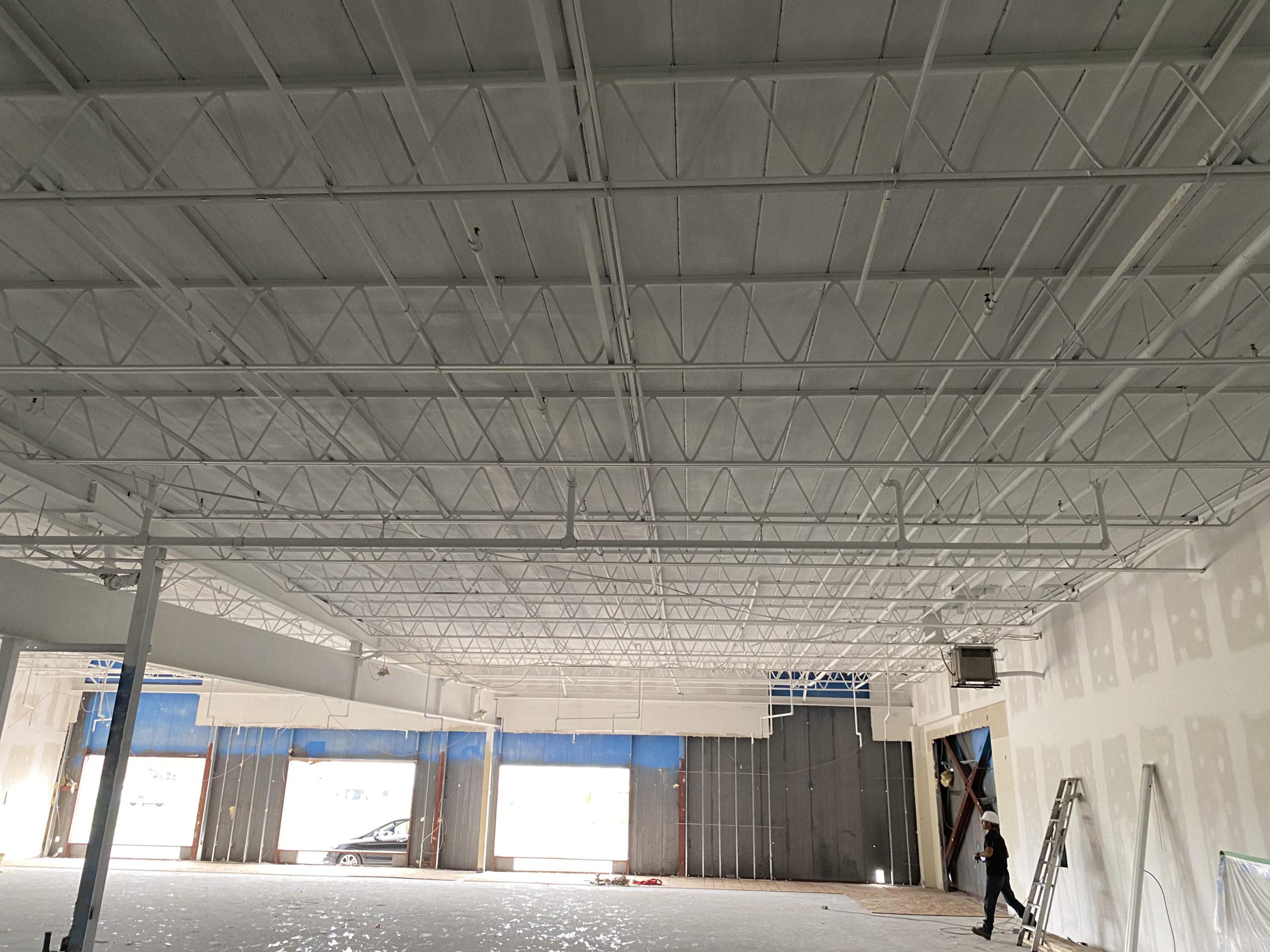 Un plafond industriel ou commercial fraîchement repeint en blanc